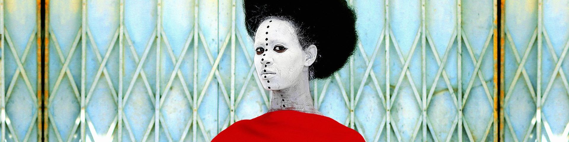 A woman stands in front of a rusting security grille. She wears a dramatic red cape and her head is framed by a halo of black hair. Her face is painted white and a line of black dots stretches from the top of her forehead to the base of her neck, which are inspired by traditional African body art.